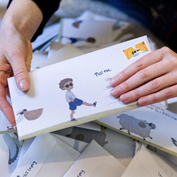 Frankierter Briefumschlag wird von zwei Händen gehalten